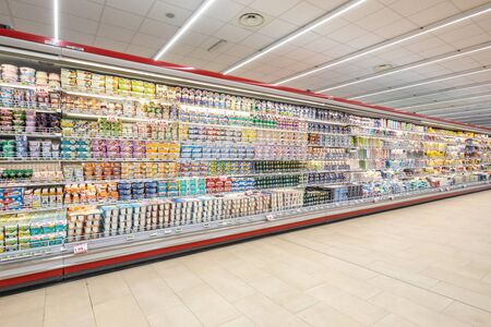 Rome / Italy. December 05, 2018: Shelving with products of different nature, variety of food displayed on the shelves inside a MA supermarket in Rome in Italy. Refrigerators with food and dairy products.