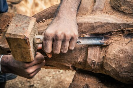 Carpenter working wood. Rudimentary tools. Two hands chiseling a piece of wood.
