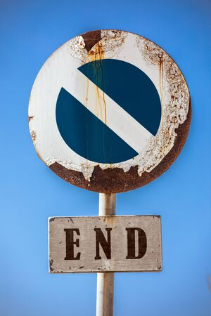 Road sign prohibiting access, at the bottom a sign with the word end. In the background a blue sky. The road sign appears damaged by the weather and rusted.