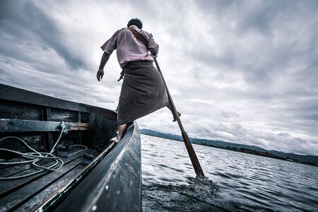 Local fishermen practicing a distinctive rowing style which involves standing at the stern on one leg and wrapping the other leg around the oar. Archivio Fotografico