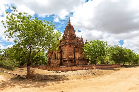 Buddhist pagoda temple. Bagan, Myanmar. Home of the largest and denset concentration of religion Buddhist temples, pagodas, stupas and ruins in the world. Blue sky with clouds.