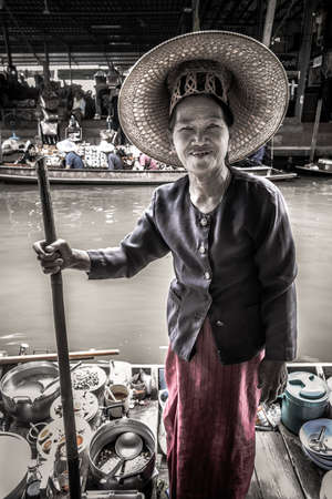 Damnoem Saduak, Thailand. Floating Market. Elderly Thai lady with typical local hat on a small boat selling her vegetable products. Looking and smiling.