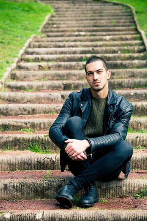 Handsome young boy sitting on a staircase in a natural park. Crouch, rock style clothes with leather jacket and dark jeans. Short hair and earring.