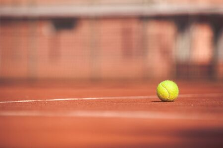 Yellow tennis ball on a clay court. Playing tennis outdoors. The ball is illuminated by the sun. Selective focus.