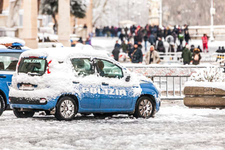 Rome, Italy. February 26, 2018: Police car covered by snow in Rome in Italy. Extraordinary wave of bad weather and cold in central Italy. Tourists walking.