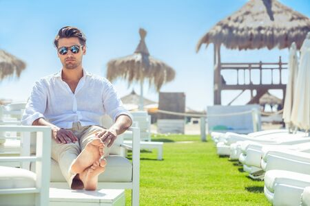 Relaxed handsome man sitting on white chairs during summer at the beach. White shirt and sunglasses. Legs stretched out.