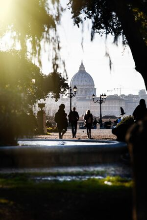 Basilica of Saint Peter seen from the Villa Borghese park in Rome, Italy. A fountain and a few tourists walking. Bright light from above. Outdoor day.
