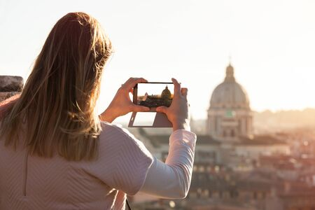 Tourist female taking picture smart phone. Travel to Rome, Italy. Tourist back woman doing a photo to the city of Rome. St. Peter 's Dome and city views from above.