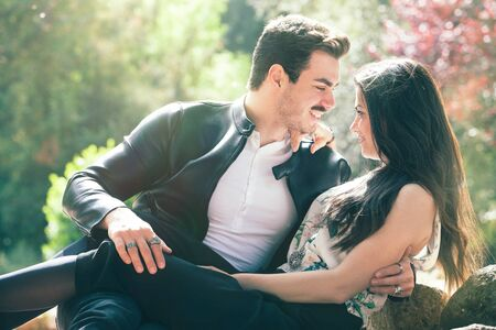 Young couple loving outdoors in a park. A young man and young woman embracing e kissing with passion and feeling. Love and falling in love. Black and white