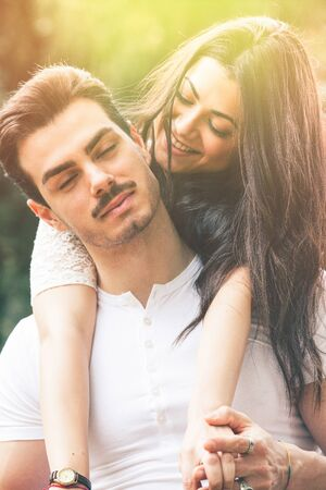 Passion and love. Couple loving. Harmony, tenderness, peace and love between two lovers. Young man and young woman embracing outdoors. Intense feeling and fiery passion. Bright light behind.