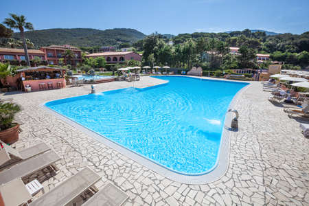 Outdoor Swimming Pool. A swimming pool and outdoor spa with poolside. Hills and green trees in the distance. Location: Procchio, Elba Island. Italy.