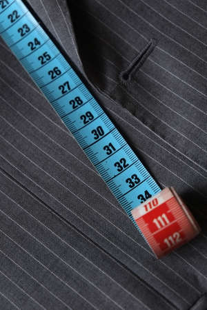 Measure tape being stretched on top of a classic gray suit coat Фото со стока - 32340566