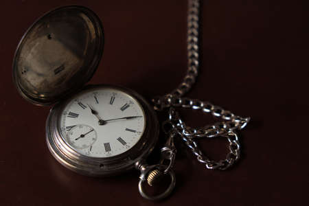 Pocket watch with chain on top of a wooden box