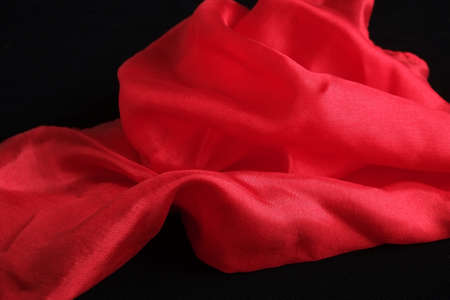 Smooth and shiny red silk handkerchief on black velvet surface