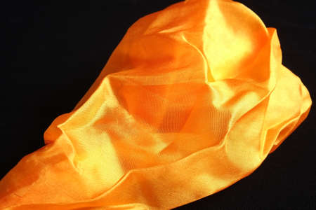 Smooth and shiny golden silk handkerchief on black velvet surface Фото со стока