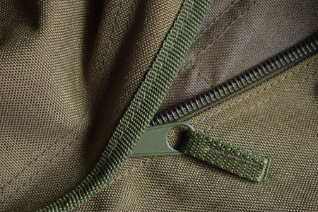 Detail of a tactical holdall army bag, showing canvas and zipper