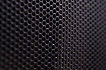 Close up of a black gray protective metal net of a speaker