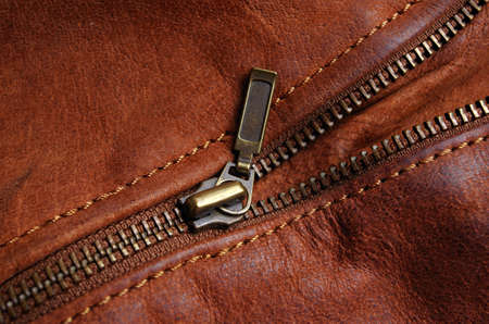 Sleeve zipper detail of a brown leather jacket, showing nylon seams