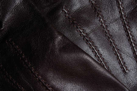 sewn up: Close up of a pair of brown leather gloves, one on top of the other, showing detail