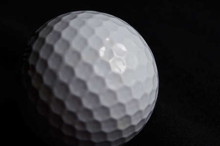 A white Golf ball on a black background