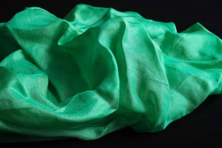 Smooth and shiny green silk handkerchief on black velvet surface