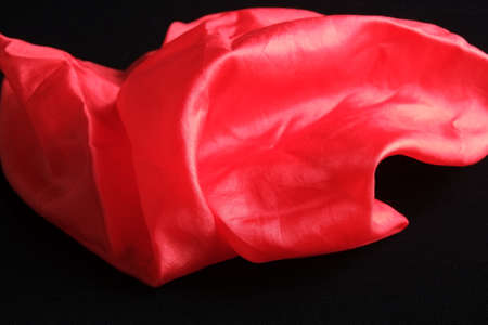 Smooth and shiny vivid red silk handkerchief on black velvet surface