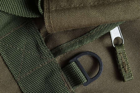 Detail of a tactical holdall army bag, showing canvas, zipper, handle and eyelet Фото со стока