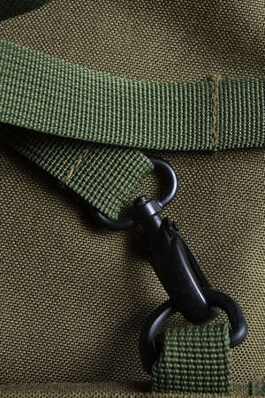Detail of a tactical holdall army bag, showing canvas and a strong black metal clasp Фото со стока