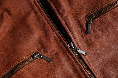 Main zipper and front pockets zippers of a brown leather jacket, showing nylon seams Фото со стока