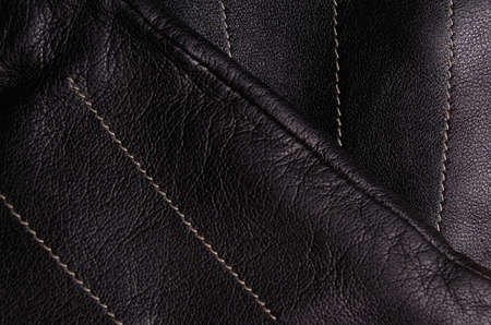 sewn up: Close up of a pair of black leather gloves, one on top of the other, showing detail Stock Photo