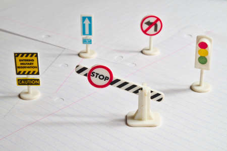 Several toy traffic signs on display on a blank sheet of paper. Driving school academy