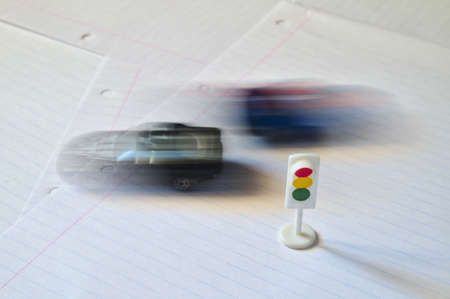 Traffic light and toy cars passing at high speed. Driving Фото со стока