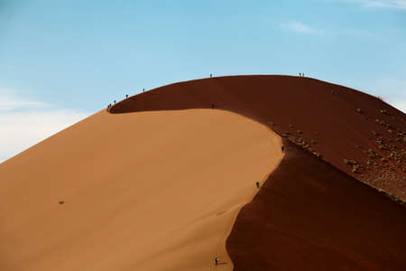 dune in the desert with people walking photo
