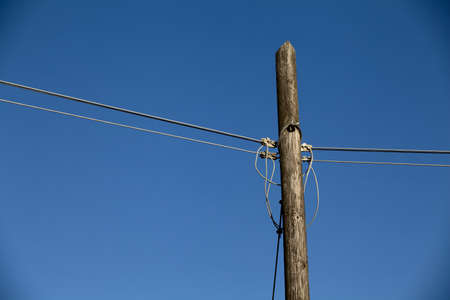Old wooden telephone pole against a gradient blue sky photo