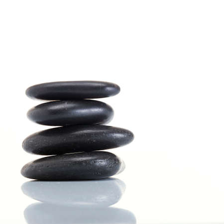 zen stone: Stack of spa hot stones isolated on white background