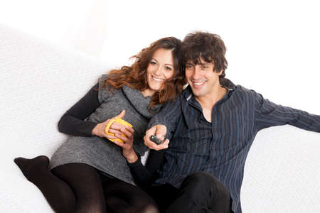 Happy couple lying down in bedroom watching television together photo