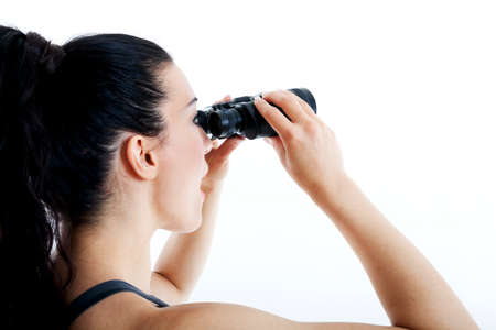 beautiful woman searching with binoculars and looking surprised photo