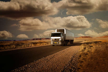 moving truck: truck traveling on a paved road in the beautiful landscape of Namibia, and the desert scene with clouds in the sky, photographed at sunset