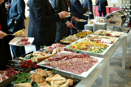 food buffet: businessmen serving themselves in a meeting event, catering set
