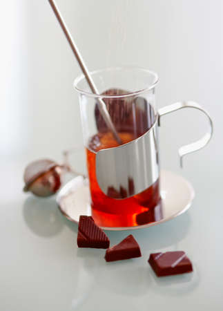 Cup of tea and chocolate on a glass table photo