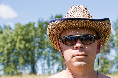 Man in sunglasses with cowboy hat at the head photo