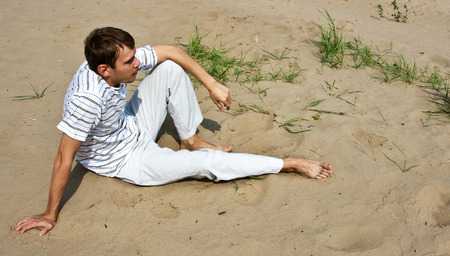 in low spirits: Low spirits man sitting on the sand