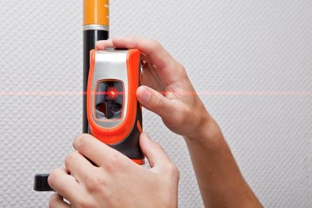 Manos de hombre de medición con gage nivel láser Foto de archivo