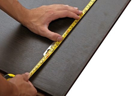 educations: Mans hand using yellow tape measure on dark wooden panel