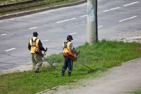 Men with lawn mower triming grass near a road.