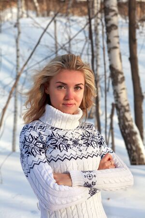 Beautiful young woman in winter clothes outdoor in forest photo