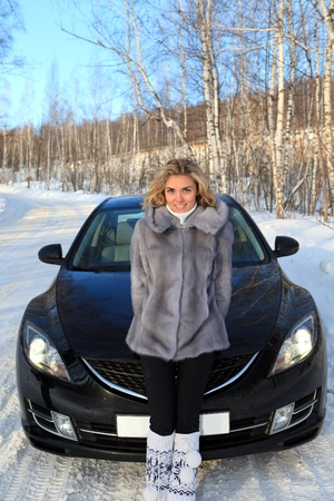Young woman near the car in Winter forest photo