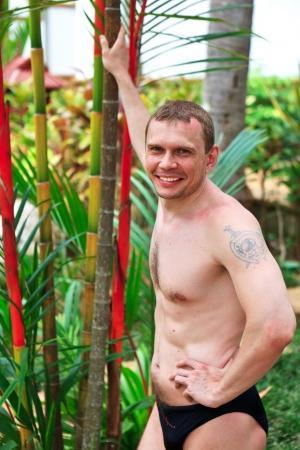 nackte brust: Junger Mann in Badehose in der Nähe eines Baumes