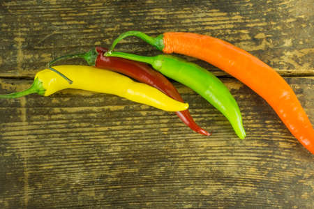 Hot peppers in various colors on a rustic wooden background Stock Photo