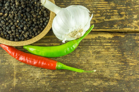 Hot peppers of different colors, black pepper and garlic on a rustic wooden background Stock Photo